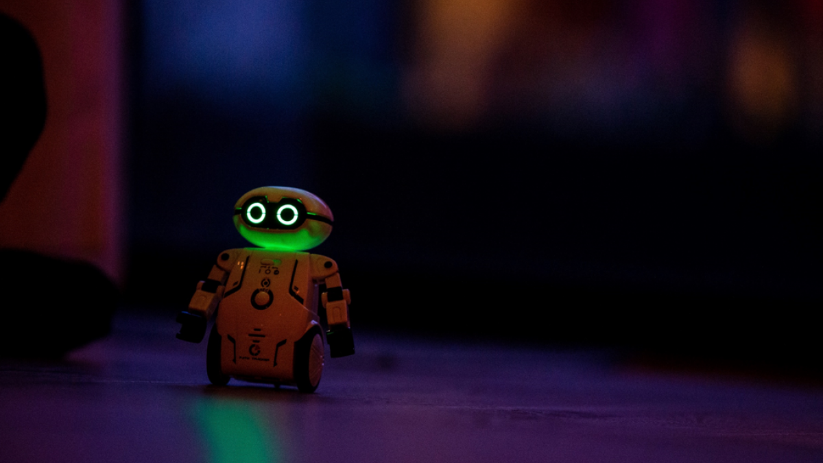 Photograph of a small, wheeled toy robot with glowing eyes against a dark background