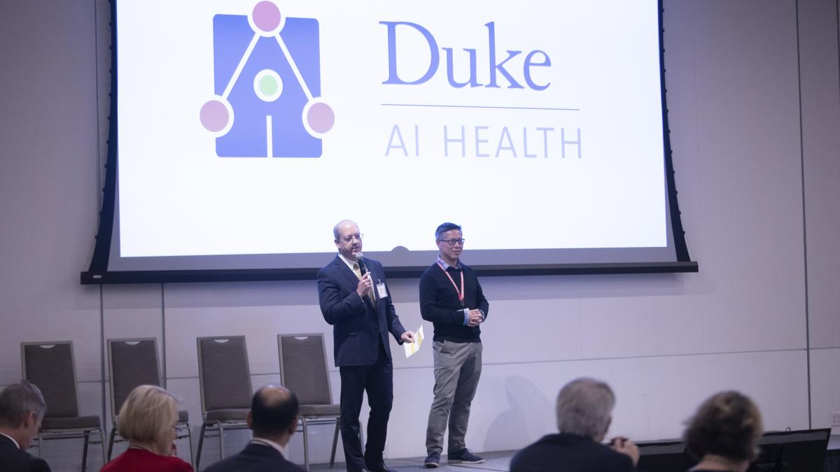 Duke University's Lawrence Carin, PhD, and Erich Huang, MD, PhD, on stage at the 2019 Duke Health Data Science Showcase, describing Duke's new AI Health initiative.