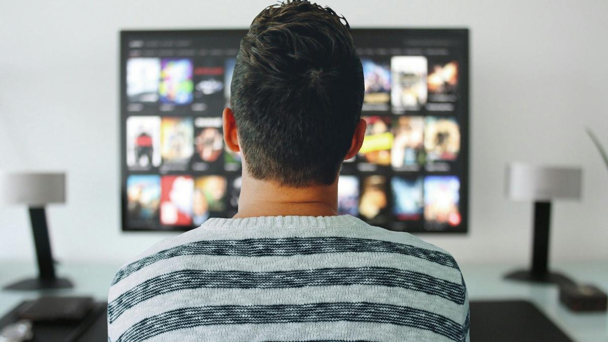 A man sitting in front of a tv screen with a lot of choices for channels