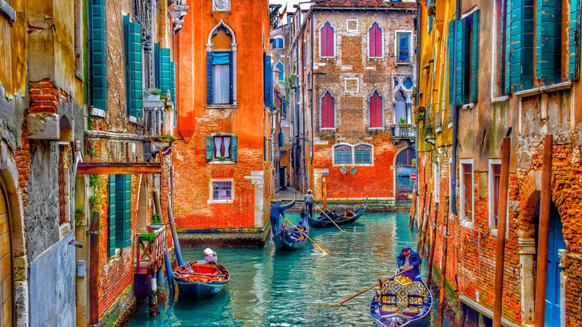 Venetian canal scene featuring gondoliers poling between brightly colored houses