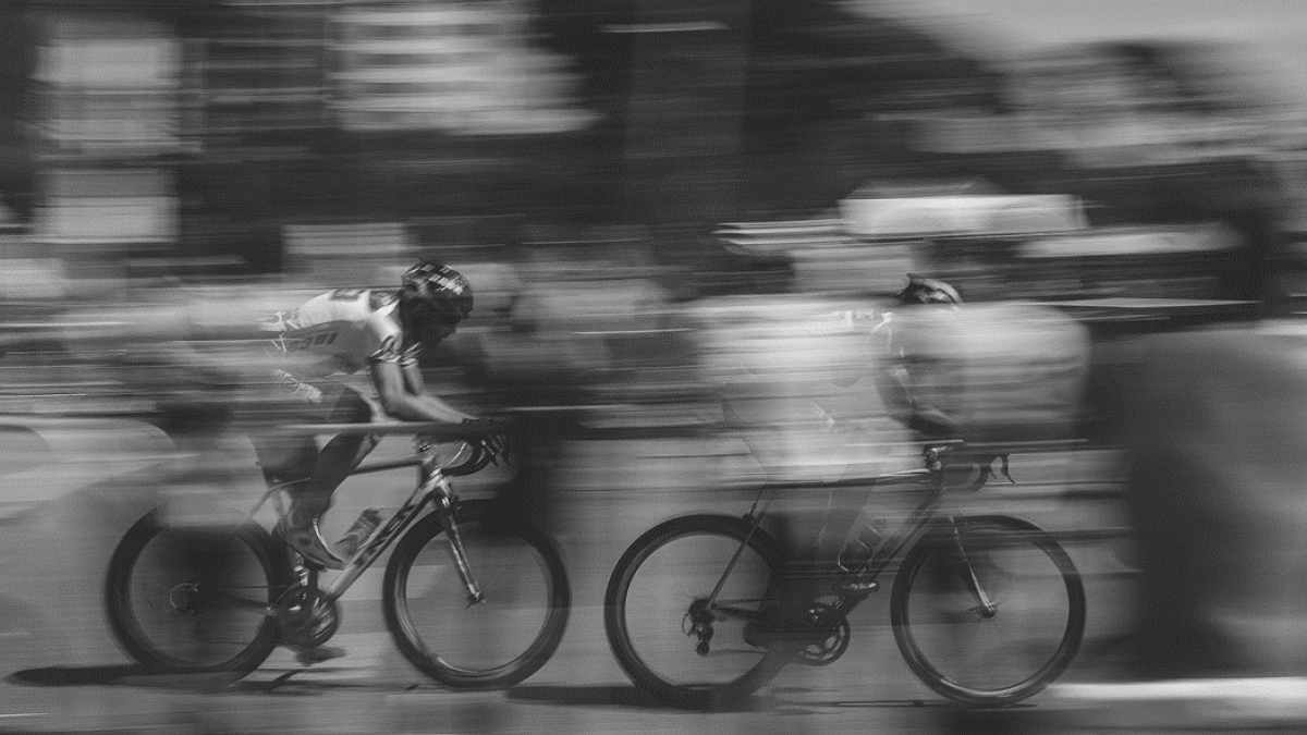 Motion-blurred black and white image of two bicycle racers at speed.