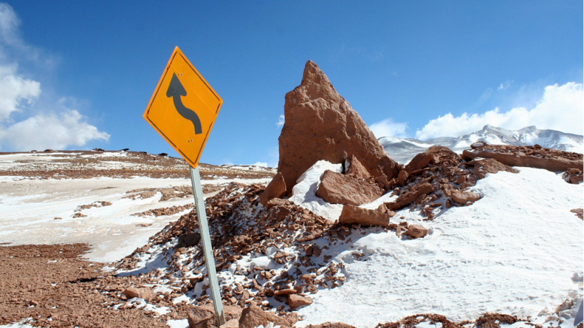 A roadsign warning of a curving road in the middle of a mountaintop snowfield. Image credit: J.C. Jimenez via Unsplash
