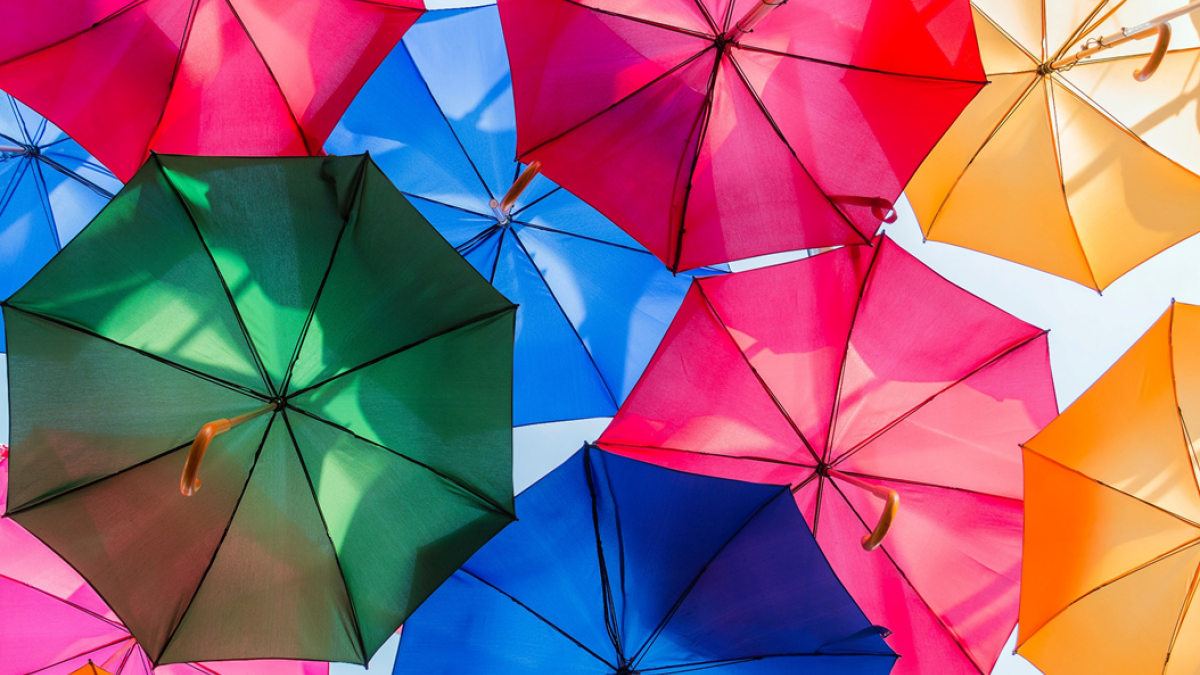 Photograph of an art installation comprising colorful open umbrellas hanging overhead. Image credit: Inset Agency via Unsplash