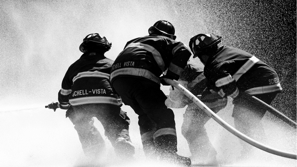 Black and white photograph of firefighters directing spray from a firehose. Image via Pixabay.