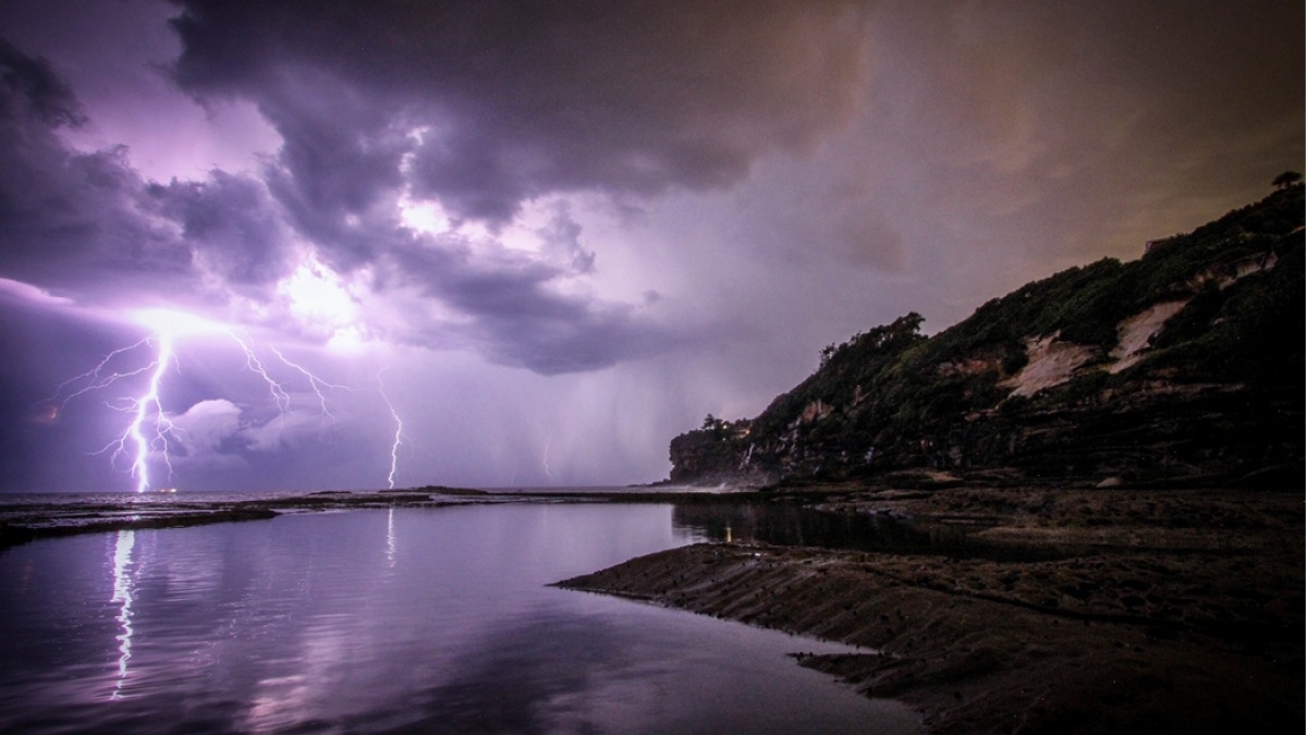 Lightning storm seen from across water, approaching bluffs of Dee Why, Australia. Image credit: Jeremy Bishop via Unsplash