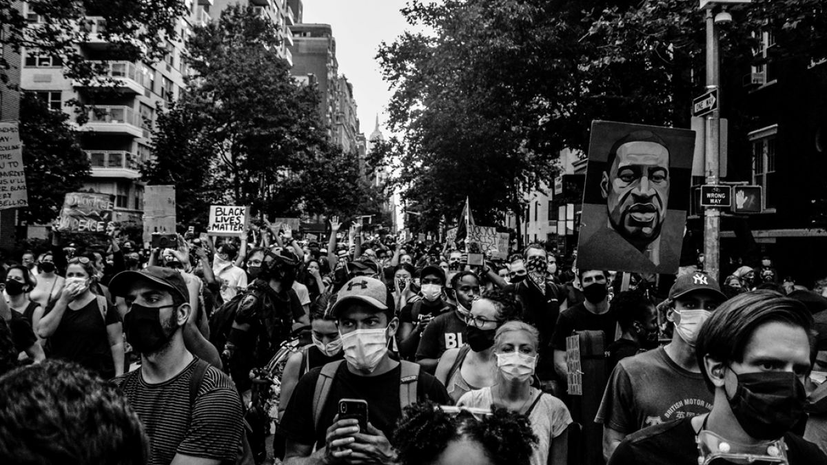 Black and white photograph of a large crowd of people, most wearing surgical masks, marching as part of a Black Lives Matter protest in New York City in August 2020. Image credit: Jakayla Toney via Unsplash