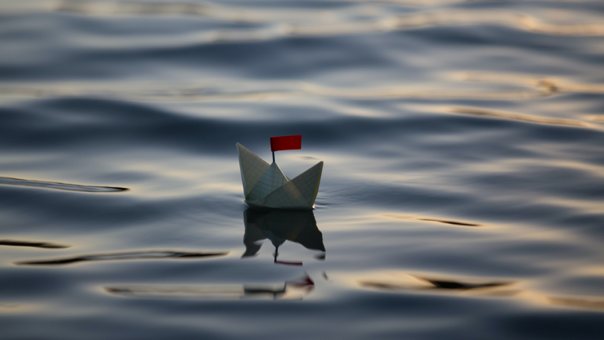 Photograph of a folded paper boat with small red flag adrift on calm water. Image credit: Artak Petrosyan via Unsplash