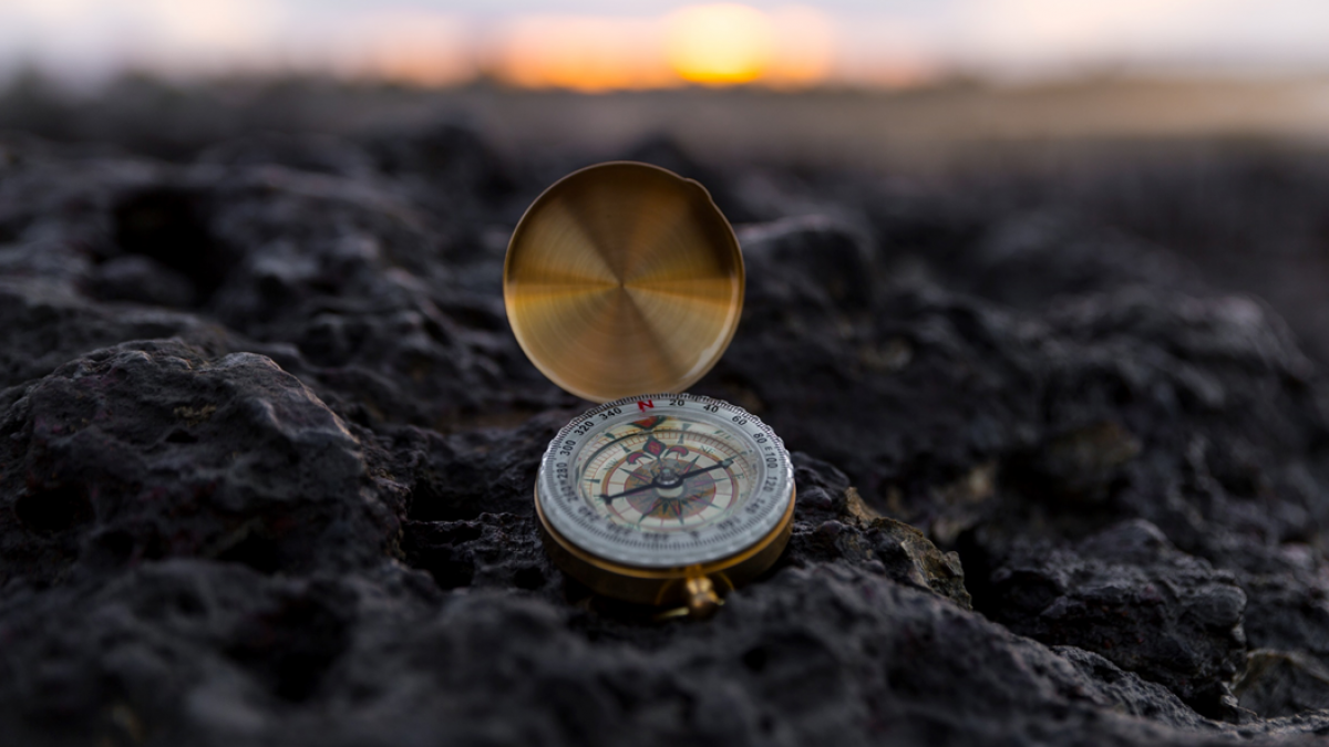 Selective focus photograph of a brass pocket compass with lid open, set on rocky ground, with the sun rising in the background. Image credit: Dunamis Church via Unsplash