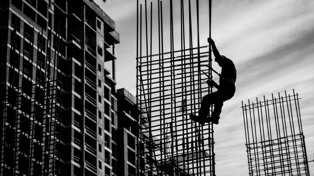 A black and white photograph of a workman, silhouetted against the sky, climbing up makeshift scaffolding with a safety harness on a building construction site. Image credit: Александр Македонский via Pexels