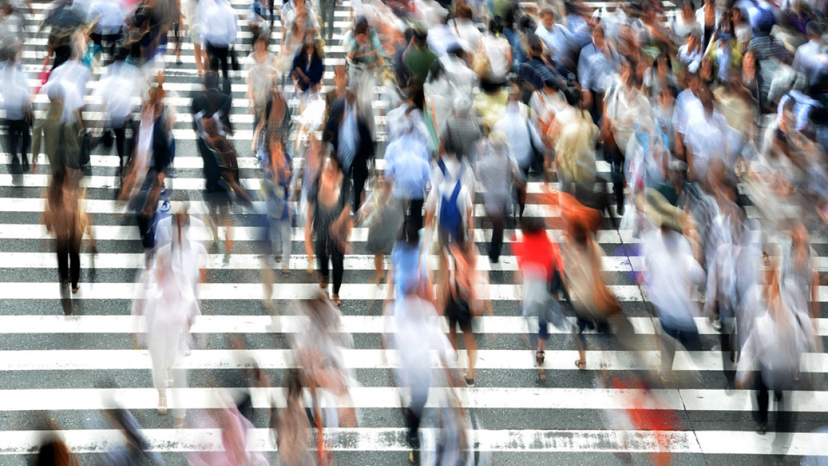 Motion-blurred photo of a large urban crowd crossing the street at a busy crosswalk.