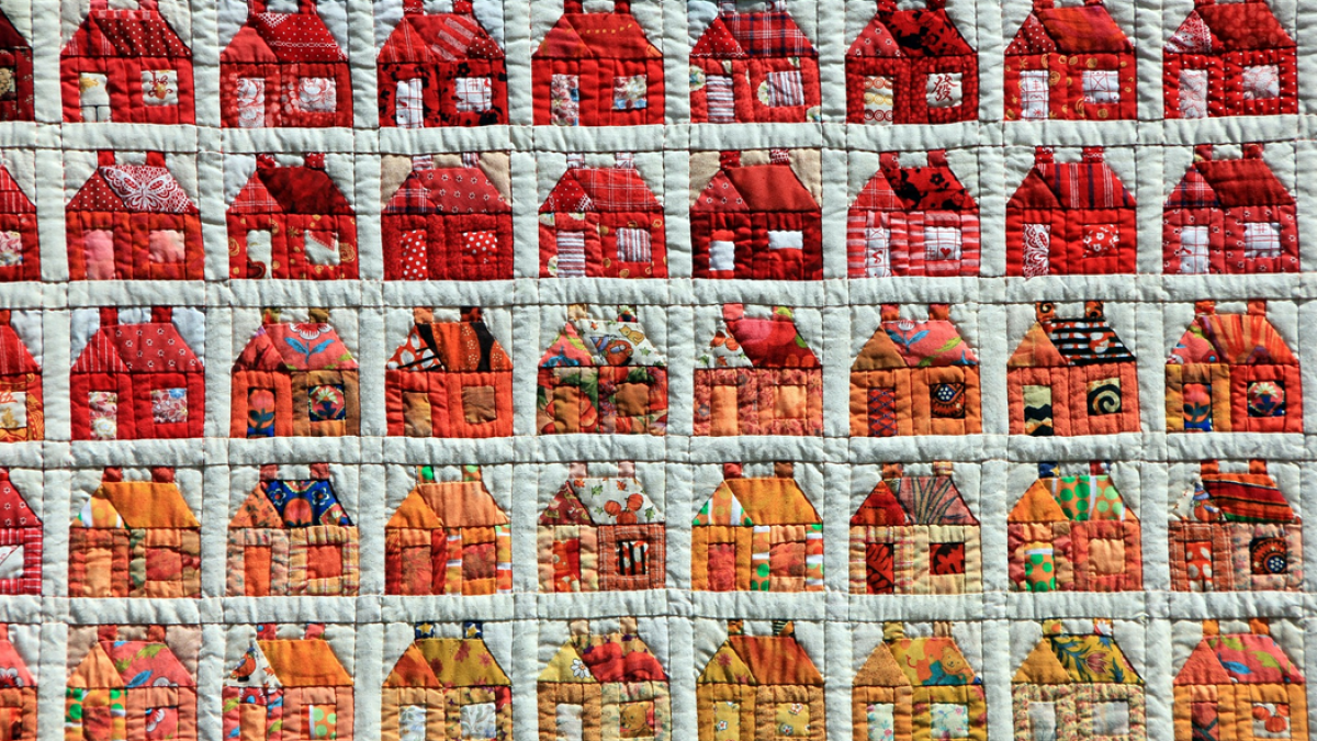 Photo of colorful patchwork quilt with a repeating pattern of houses. Image credit: AnnaER via Pixabay