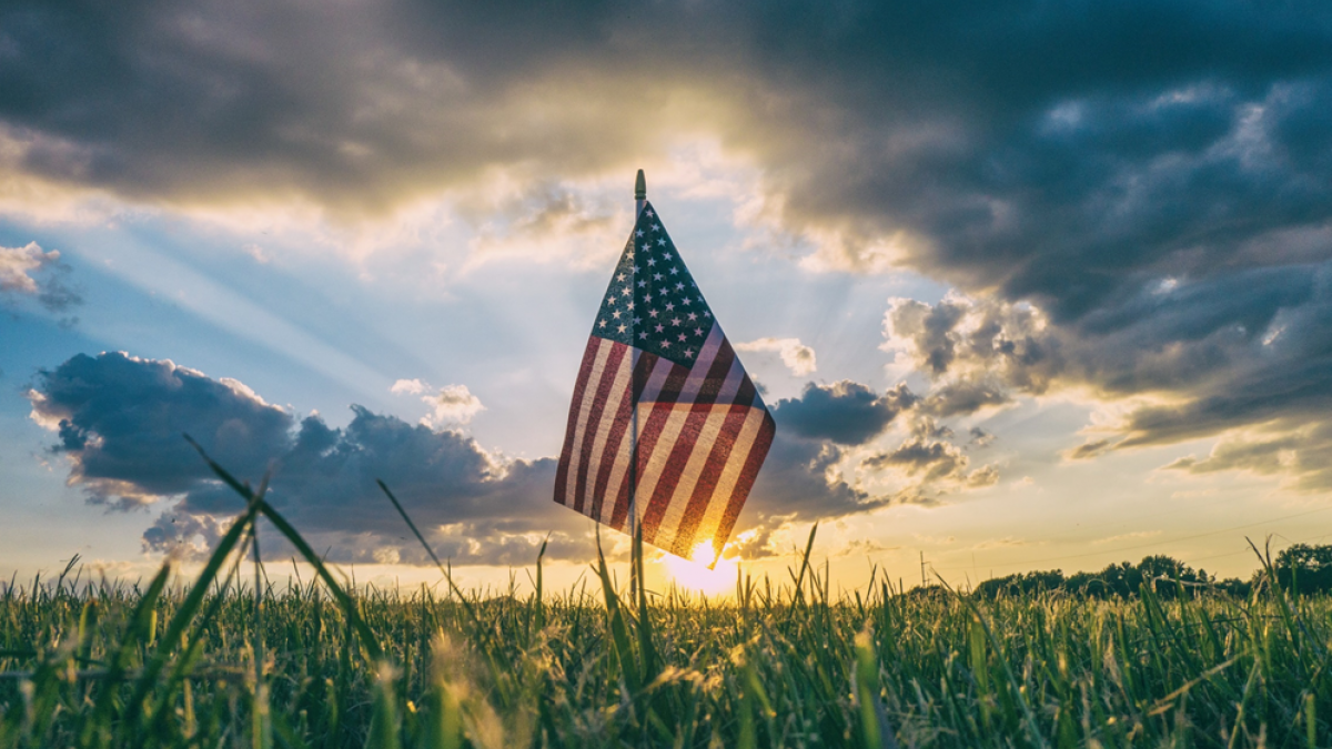Low angle photograph of a small American flag stuck into a grassy field with sunset with clouds in the background. Image credit: Aaron Burden via Unsplash