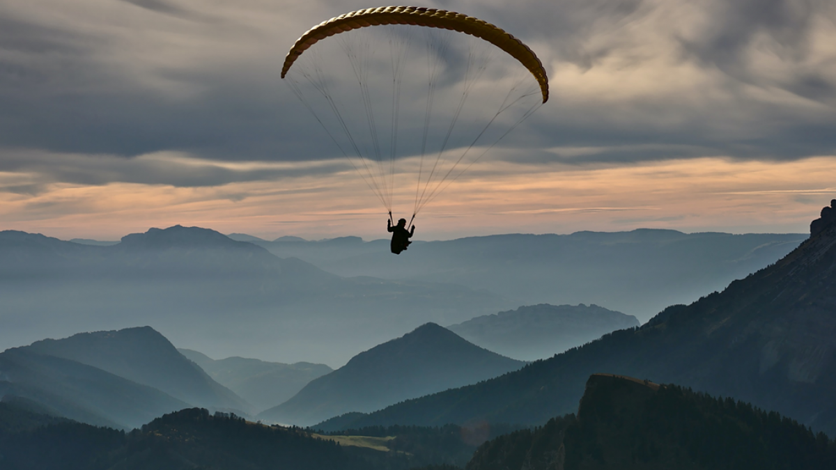 Wide angle photograph of a person parachuting over a mountain range with clouds and mist. Image credit: Nicolas Tissot/Unsplash