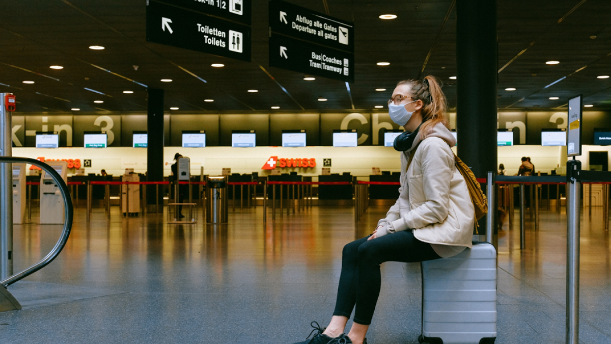 Woman wearing a surgical mask sits on her luggage in an otherwise empty airport. Image credit: Anna Shvets via Pexels.