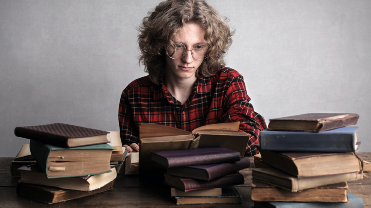 Young man with large round glasses searching through a pile of books on a table in front of him. Image credit: Andrea Piacquadio via Pexels