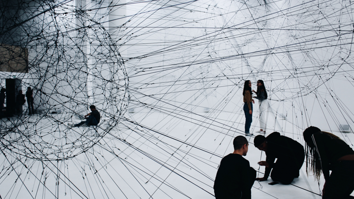 Black and white photograph of an art installation comprising a webwork of lines and cables stretched across a large white room, with a small cluster of people kneeling at one corner.