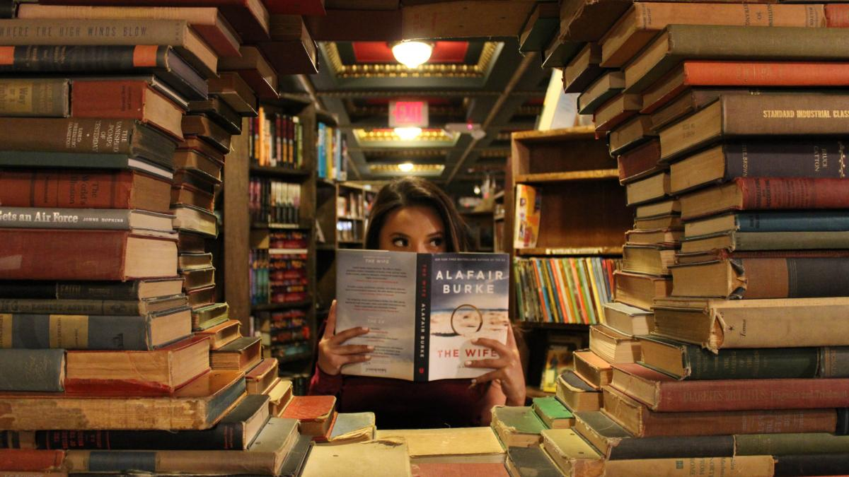 Woman behind a stack of books reading