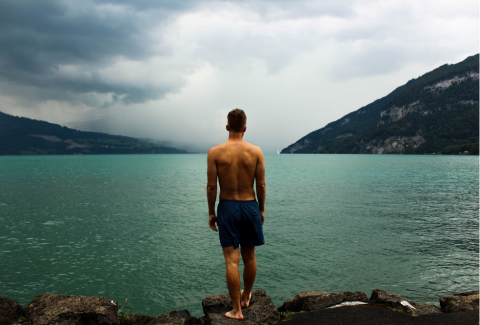 A man wearing swimming trunks standing with back to camera on a rocky lake shore framed by hills. Image credit: William Ferguson via Unsplash