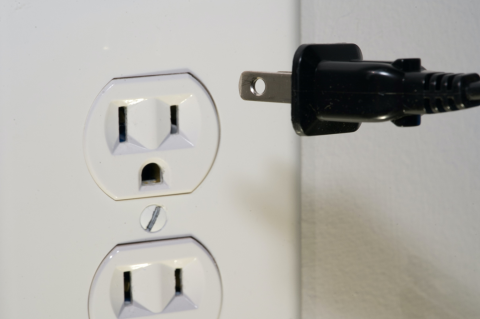 Close-up photo of an American 110-volt wall outlet with a two-pronged plug being inserted into one of the sockets. Image credit:  Clint Patterson via Unsplash