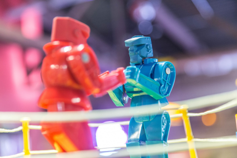 Two brightly colored toy robots face off as if in a boxing match. Image credit: Lorie Shaull via Wikimedia Commons (CC BY-SA 4.0)
