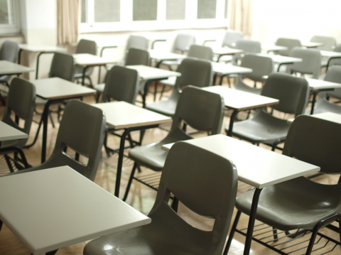 Desks and chairs in neat rows in a classroom with no students or teachers in it. Image credit: MChe Lee via Unsplash